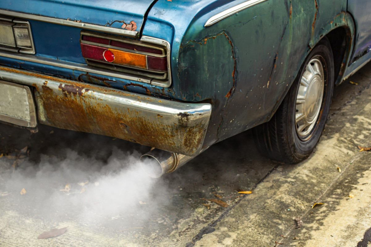 rusted car with smoke coming out of exhaust